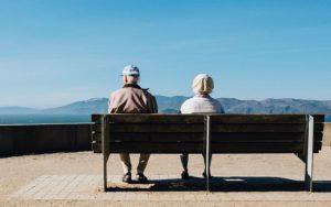 Older couple sat on a bench enjoying longer life expectancy